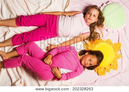 Children With Smiling Faces Lie Close On Pink Blanket Background