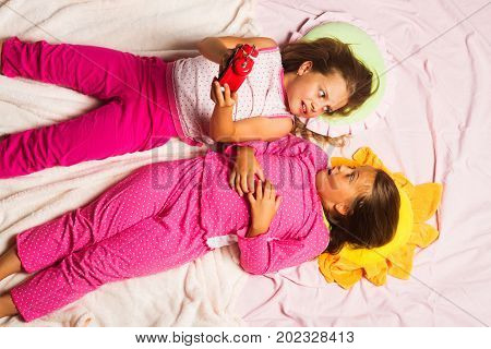 Children with scared faces hold alarm clock look at each other. Childhood and oversleeping concept. Schoolgirls over slept on funny pillows and pink background. Kids in pink pajamas hold red clock