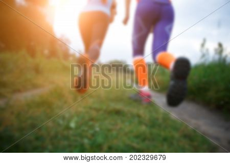 Blurred photo of two running women along path in park