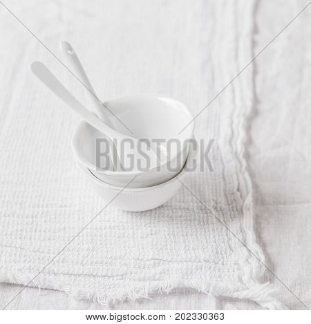 Two Porcelain Bowls and Teaspoons over White Cloth Background square