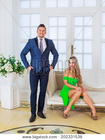 attractive man and woman posing in the luxurious interior