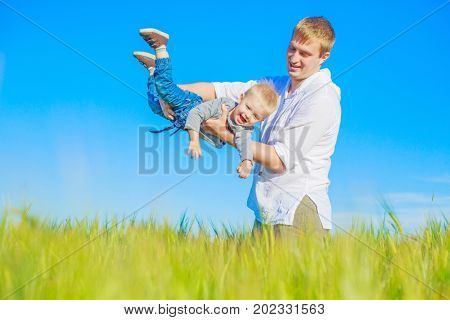 happy young father and a son  in the wheat field