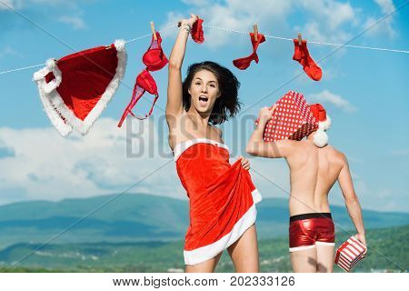 Xmas red costume on rope with pin. Couple in love of man and girl hanging clothes for drying. New year guy with muscular body on blue sky. Laundry and dry cleaning. Christmas man and woman family.