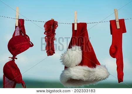 Christmas clothes outdoor. New year costume on blue sky. santa clothes for drying. Laundry and dry cleaning. Xmas red costume on rope with pin.