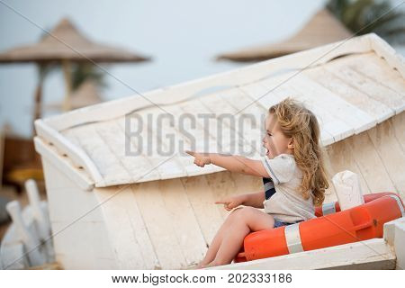 Marine safety and transport. Childhood and baby care concept. Travel and summer vacation. Child little boy little sitting in life buoy on boat. Small kid pointing with pointer finger at beach.