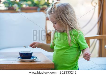 Childhood and baby care concept. Boy child mixing sugar in blue cup. Little kid boy making tea. Child boy with blond long hair mixing sugar with teaspoon. Healthy breakfast for child.
