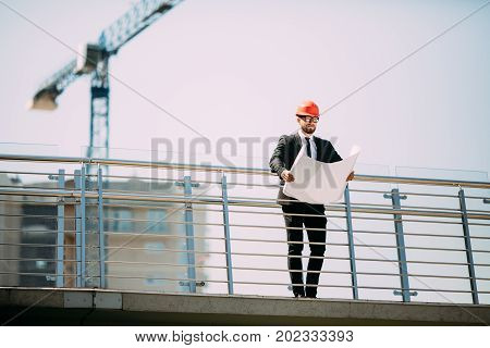 Handsome Man Engineering Consulting People On Construction Site Holding Blueprint In His Hand. Build