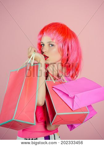 Fashion shopper posing on pink background. Girl wearing red wig and fashionable clothes. Sale and black friday. Holidays celebration concept. Woman with shopping bags.