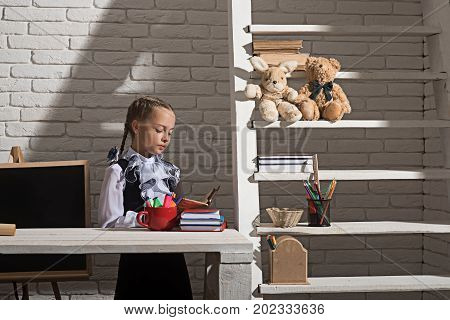 Schoolgirl with concentrated face holds open book. Classroom and study time concept. Girl at her desk with colorful stationery and books. Kid near blackboard and shelf on white brick wall background
