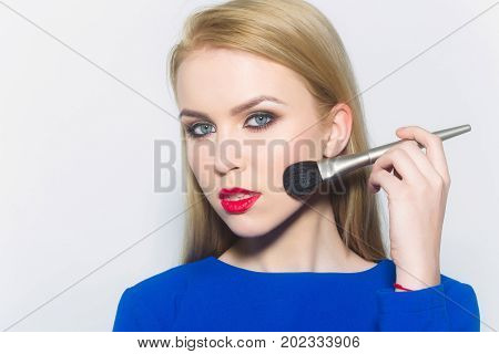 Girl with red lips applying makeup on face skin with powder brush. Sexy woman with blond long hair in blue dress on white. Fashion. Visage make up cosmetics and skincare