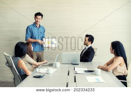 Asian businessman present sell graph at meeting room in office. Business present and meeting concept.