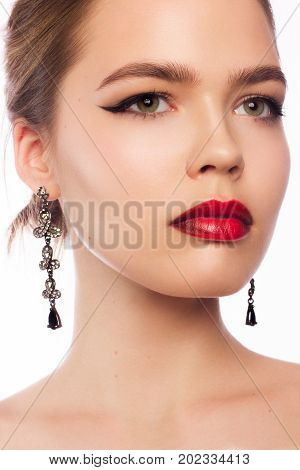 Beauty and fashion of the woman with chubby red lips and shooters of a pencil in the eyes. Magnificent eyelashes eyebrow mascara and magnificent jewelry earrings. Beautiful long neck pure leather