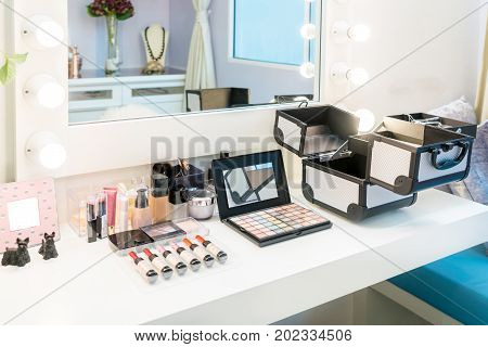 Cosmetic set with eye shadow eye liner and powder on wood dressing table in home. Makeup brush and cosmetics for beauty.