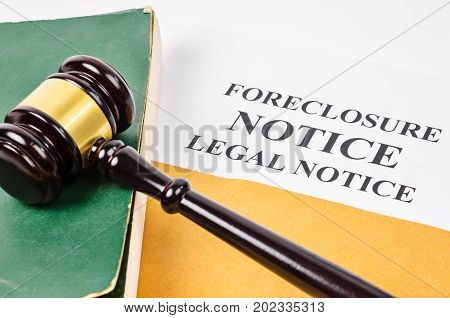 Gavel and Foreclosure Notice document with old book.