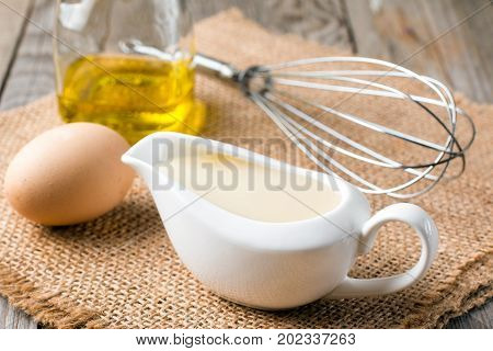 Fresh homemade white sauce Mayonnaise and ingredients eggs lemon olive oil on wooden background