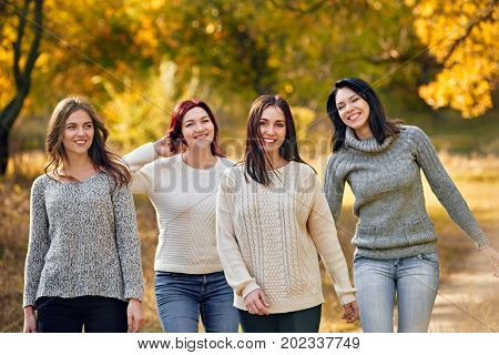 Pretty happy girls walking through autumn park