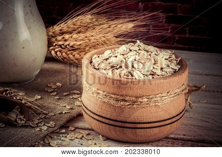 Fresh dairy products and wheat on rustic wooden background.