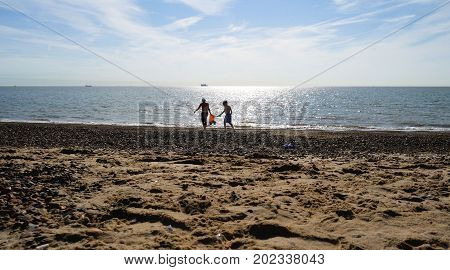 Teen Boy helping his brother at British Seaside.