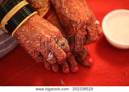 A hindu bride adjusting the traditional ring in her feet with her hand having beautiful mehendi design