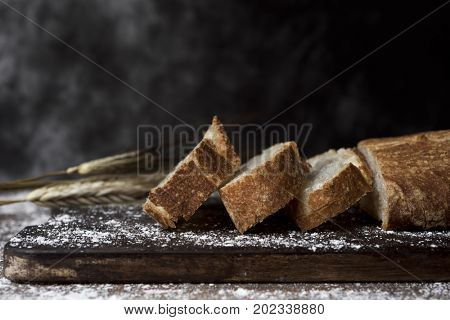 closeup of a loaf and some slices of pa de vidre or pa de coca, a bread typical of Catalonia, Spain, on a rustic wooden table