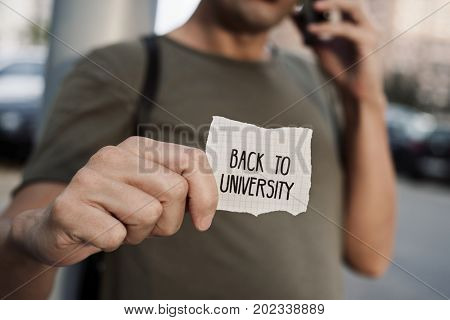 closeup of a caucasian student outdoors with a note with the text back to university written in it