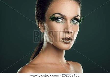 beauty portrait of attractive woman with large patch of green eyelashes feather