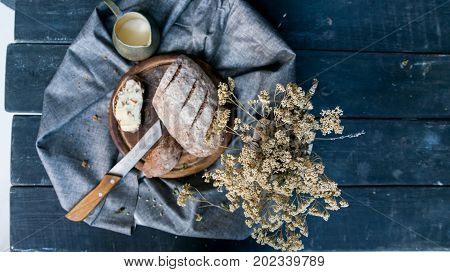 Top view rye bread with butter sandwich, knife, mug with coffee and dry flowers in vase -- beautiful breakfast image on dark background
