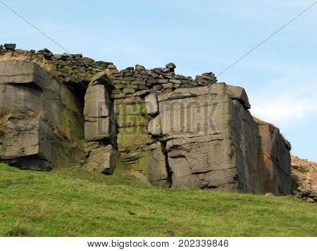 rocky outcrops boulders and stone walls in yorkshire moorland
