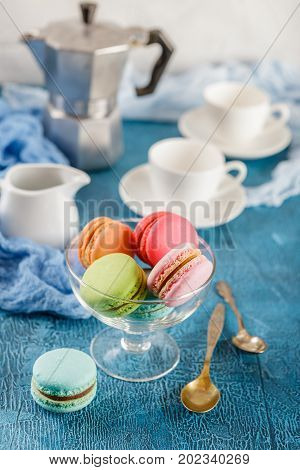 Classic French colorful mackerel cookies in glass vase, cups for coffee and metal coffee maker on blue background
