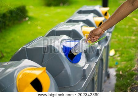 Young Girl Hand Dropping Plastic Bottle Into Recycle Bin And There Are Waste Separation Bin For Diff