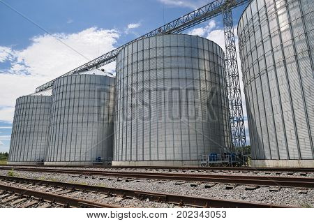 Agricultural Silos. Metal grain facility with silos. Storage and drying of grains wheat corn soy sunflower against the blue sky with white clouds
