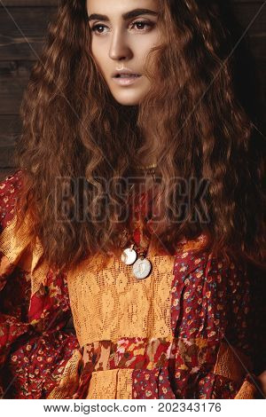Beautiful young woman with long curly hairstyle fashion jewelry with long brunette hair. Sexy girl in vogue style. Pretty arabian beauty portrait of female face. Indian style clothes long dress