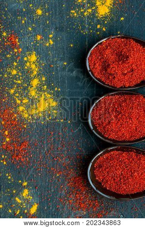 Top view of spoons filled with red paprika spice on dark wooden background covered with paprika and turmeric powder
