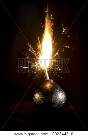 An old round bomb with a firing wick on a black background