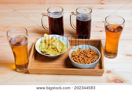 Beer mugs and glasses on wooden table. Beer snacks are chips and pretzels. Drink and snack for football match or party. Selective focus