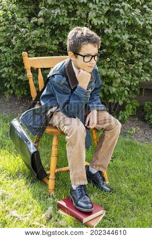 Preteen Boy Dressed In Smart Vintage Style Sitting On Chair Outdoors Thinking
