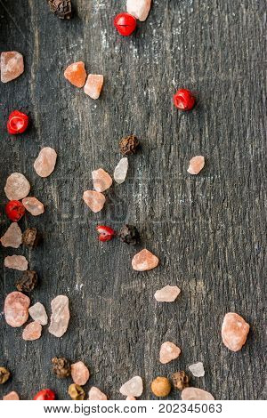 Close up grains of pink himalayan salt mixed with pink and red peppercorn on dark wooden surface