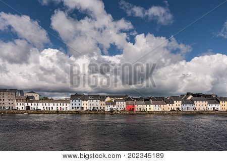 Galway Ireland - August 5 2017: Closeup of lIne of colorful houses of The Long Walk quay under enormous white clouds in blue sky and with dark blue water of the port in front.