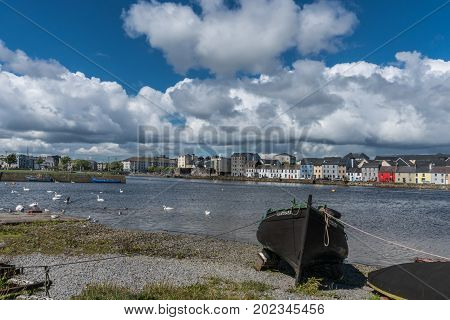 Galway Ireland - August 5 2017: Enormous white cloudscape in blue sky over section of The Long Walk quay. Up front black boat on shore. Dark water in between with white swans and seagulls.