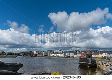 Galway Ireland - August 5 2017: Enormous white cloudscape in blue sky over section of The Long Walk quay. Up front black ship wreck on dark water.