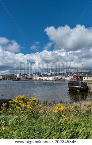 Galway Ireland - August 5 2017: Portrait of enormous white cloudscape in blue sky over section of The Long Walk quay. Up front black ship wreck on dark water in between. Up front wild yellow flowers and green.
