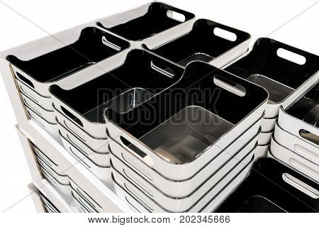 Stack of black plastic trays arrangement for background. Multi-purpose kitchenware collection