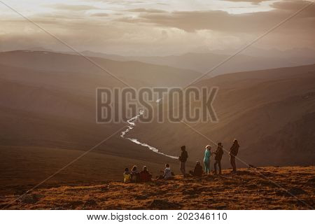 Big group of friends on mountain's top having rest and looging at sunset. Space for text
