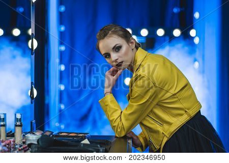attractive girl with makeup in yellow leather jacket standing at mirror with light bulbs
