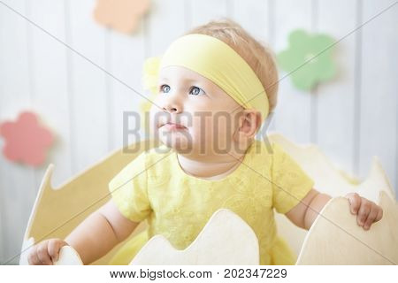 photo of little girl in yellow dress with headband at the eggshell