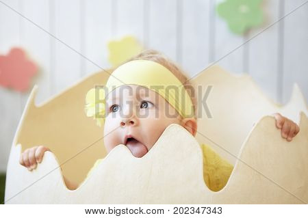 photo of little girl at the eggshell licking the shell