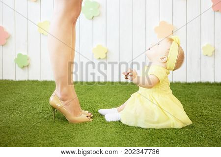 photo of little girl in yellow looks up at mom