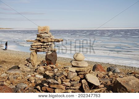 Inukshuk or Inuksuk on a rocky beach with ice on the ocean in late June in the high arctic near the community of Cambridge Bay