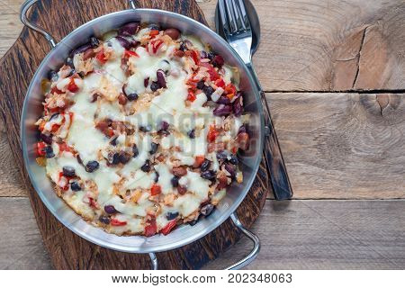 Baked rice casserole with different kinds of beans cheese and paprika in metal baking dish horizontal top view copy space