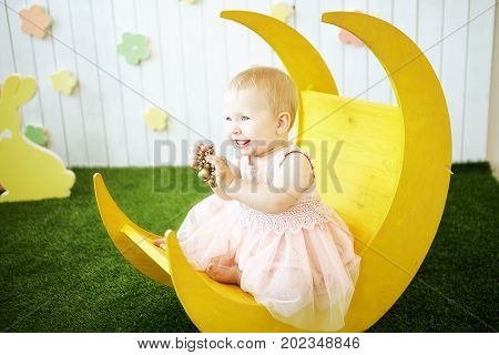 photo of little girl in yellow dress with decoration in her hair at the moonchair